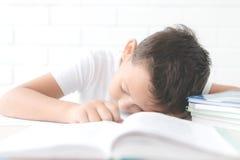 男孩在家做他的家庭作业在他的书桌 免版税图库摄影