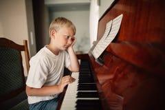 男孩在家弹钢琴 免版税图库摄影