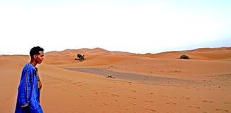 男孩在尔格沙漠的沙丘berried在摩洛哥 库存照片