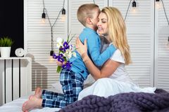 男孩在床上叫醒妈妈并且给她一花束 庆祝妇女的天 日母亲s 免版税库存照片