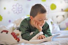 年轻男孩在床上的读一本书 免版税库存照片