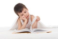 男孩在床上读了一本书 免版税库存照片