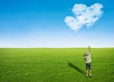 男孩在心脏形状的领域云彩  库存照片