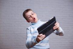 男孩在打大字了书写在他的片剂的网络游戏 小配件, inte 免版税库存图片