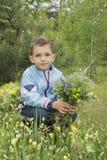 男孩在拿着花的花束森林里 免版税库存图片