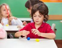 男孩在教室的造型黏土 免版税库存照片