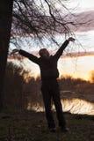 男孩在日落站立 免版税库存图片