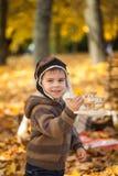 年轻男孩在有一架小木飞机的秋天公园 免版税库存照片
