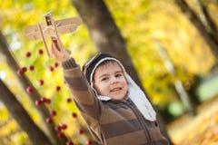 年轻男孩在有一架小木飞机的秋天公园 免版税库存图片