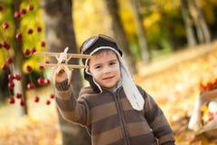 年轻男孩在有一架小木飞机的秋天公园 库存图片