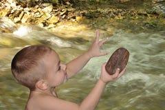 男孩在有岩石的河 库存图片