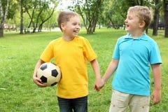 男孩在有球的公园 图库摄影