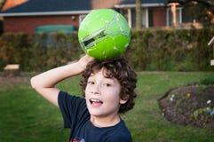 男孩在有球的后院 库存图片