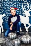 男孩在有礼物的圣诞老人帽子 圣诞节和新年concep 免版税库存照片