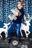男孩在有礼物的圣诞老人帽子 圣诞节和新年concep 免版税库存图片