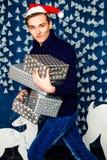 男孩在有礼物的圣诞老人帽子 圣诞节和新年concep 库存照片