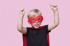 年轻男孩在有胳膊的超级英雄服装穿戴了被举在桃红色背景 免版税库存图片