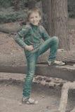 男孩在有他的腿的杉木森林里在日志 免版税图库摄影