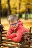 年轻男孩在木篱芭附近的秋天公园 免版税库存照片