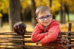 年轻男孩在木篱芭附近的秋天公园 库存照片