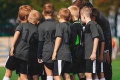 男孩在杂乱的一团的足球队员 孩子炫耀与教练的足球队汇聚在运动会比赛地点 免版税库存图片