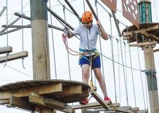 男孩在森林冒险公园 在橙色盔甲的孩子和在高绳索足迹的白色T恤杉攀登 上升室外,娱乐中心 免版税库存照片