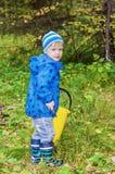 男孩在森林里会集蘑菇 免版税库存图片
