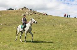 男孩在歌曲Kul湖骑马在吉尔吉斯斯坦 库存图片