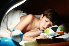 男孩在毯子下的阅读书在夜 免版税库存照片