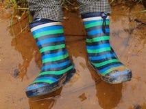 年轻男孩在池塘中泥泞的水洗涤胶靴  坏的沙子 免版税库存照片