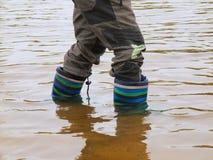 年轻男孩在池塘中泥泞的水洗涤胶靴  坏的沙子 图库摄影