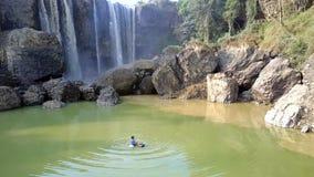 男孩在池塘钓鱼坐lifebuoy由瀑布 股票视频