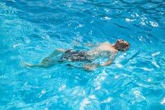 男孩在池游泳 免版税库存图片