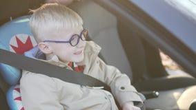 男孩在汽车座位的汽车坐 他折了 股票录像