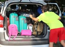 男孩在汽车的后车箱装载行李 库存照片
