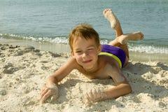 男孩在沙子说谎。 免版税库存图片