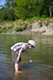 男孩在河使一条小船下水 免版税库存图片
