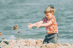 男孩在海和投掷沙子使用在海滩 库存图片