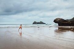 男孩在海洋海滩追捕雨 免版税图库摄影