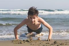 男孩在海滩的沙子绞了在海背景 体育的概念 免版税库存照片