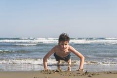 男孩在海滩的沙子绞了在海背景 作为背景诱饵概念美元灰色吊异常分支 库存照片