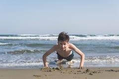 男孩在海滩的沙子绞了在海背景 作为背景诱饵概念美元灰色吊异常分支 免版税库存照片