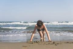 男孩在海滩的沙子绞了在海背景 作为背景诱饵概念美元灰色吊异常分支 免版税库存图片