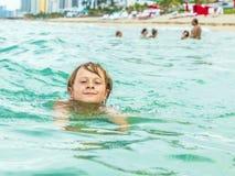 男孩在海洋游泳 免版税库存图片