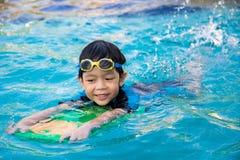男孩在游泳池学会游泳 免版税库存照片