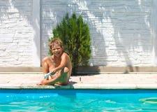 男孩在游泳池附近坐 库存图片