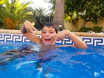 男孩在游泳池飞溅 免版税库存图片