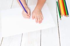 男孩在白色在他的手上拿着一支色的铅笔并且画 免版税库存照片