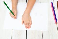 男孩在白色在他的手上拿着一支色的铅笔并且画 库存图片