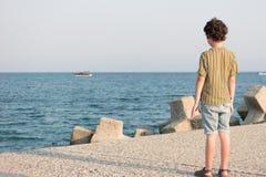 男孩在码头站立 免版税库存照片